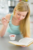 Woman eating yogurt and reading book — Stock Photo