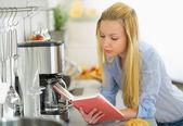 在厨房里的女人看书 — 图库照片