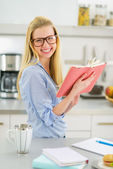 Woman studying in kitchen — Stock Photo