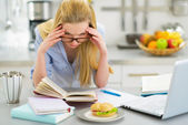 Stressed young woman studying in kitchen — Stock Photo