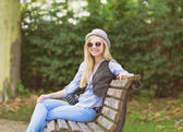 Young hipster sitting on bench — Stockfoto