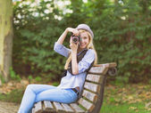 Young hipster taking photo with retro photo camera sitting on be — Stockfoto