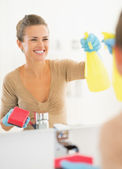 Housewife cleaning mirror in bathroom — Stok fotoğraf
