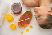 Woman near honey spa therapy ingredients — Stock Photo