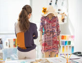 Fashion designer looking on garment — Stock Photo