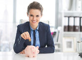 Business woman putting coin into piggy bank — Stock Photo