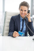Business woman with credit card talking phone — Stock Photo