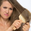 Frustrated young woman combing hair — Stock Photo #44698251