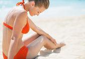 Giovane donna seduta sulla spiaggia — Foto Stock