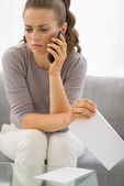 Concerned woman with letter and phone — Stock Photo