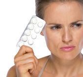 Thoughtful young woman with pills — Stock Photo