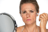 Woman applying plastic surgery marks — Stock Photo