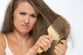 Frustrated young woman combing hair — Stock Photo