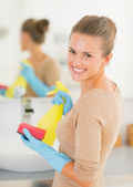 Housewife with spray bottle and sponge — Stock Photo