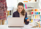 Fashion designer with credit card using laptop — Stock Photo
