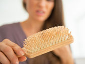 Woman looking on hair comb — 图库照片