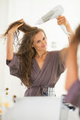 Woman blow drying hair — Photo