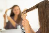 Woman combing hair in bathroom — Stock Photo