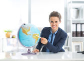 Business woman pointing on globe — Stock Photo