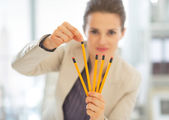 Business woman choosing from pencils — Stock Photo