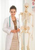 Lékař žena poblíž lidská kostra — Stock fotografie