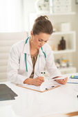 Medical doctor woman writing in clipboard — Stock Photo