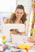 Happy young woman making easter pot holder mitts — Stock Photo