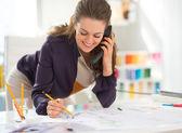 Fashion designer in office talking phone — Stock Photo