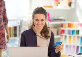 Fashion designer using laptop with credit card — Stock Photo