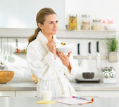 Woman eating muesli in kitchen — Stock Photo