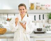 Woman eating muesli in kitchen — Stock Photo