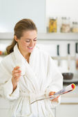 Frau trinkt milch in küche — Stockfoto