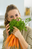 Young housewife holding carrot — Stock Photo