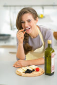Happy housewife eating cheese with olives — Stock Photo