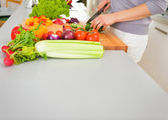 Young housewife cutting vegetables — Stock Photo