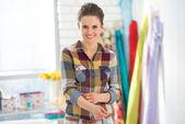 Smiling seamstress in studio — Stock Photo