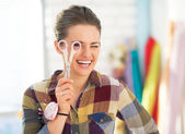 Smiling seamstress using looking through scissors — Stockfoto
