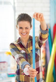 Happy seamstress using measuring tape — Stock Photo
