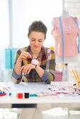 Seamstress taking needle from pincushion — Stockfoto