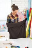Seamstress looking on fabric in studio — Stock Photo