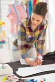 Seamstress making pattern on fabric — Stock Photo
