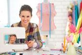 Happy seamstress sewing in studio — Stock Photo