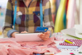 Seamstress with credit card using tablet pc — Stock Photo