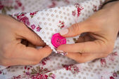 Closeup on seamstress sewing button — Stock Photo