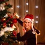 Beautiful woman hanging Christmas ball on Christmas tree — Stockfoto #8653135