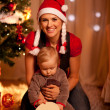 Adorable baby near Christmas tree opening Christmas gifts with m — Stock Photo #8653358