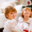 Portrait of happy girl playing with sister near Christmas tree — 图库照片 #8657881