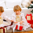 Two happy twins girl opening presents near Christmas tree — 图库照片 #8657888