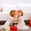 Twin girl kissing her sister near Christmas tree with gifts — Stock Photo #8657890