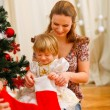 Mom looking with daughter inside of Christmas socks near Christm — Stock Photo #8997003